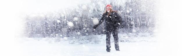男はバックパックを持って旅行します。森の中の冬のハイキング。公園で冬の散歩の観光客。