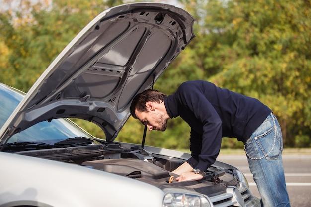 Мужчина пытается починить машину на дороге