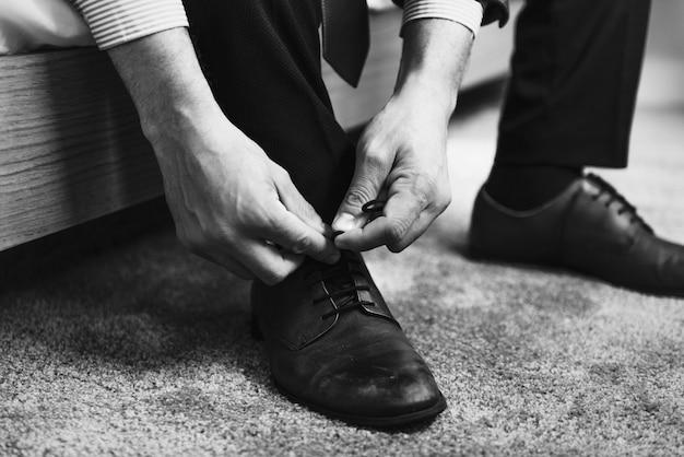 靴ひもを結んでいる男