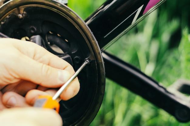 Мужчина откручивает болты с помощью оранжевой отвертки на цепи горного велосипеда