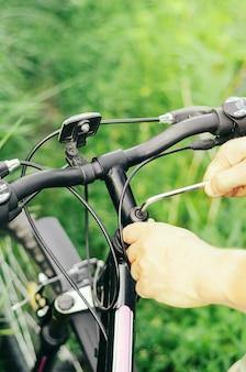 Мужчина отвинчивает болты шестигранным ключом на руле горного велосипеда