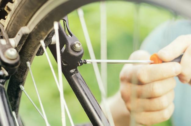 男は草の上のマウンテンバイクのマウントホイールブレーキのドライバーでボルトを緩めます
