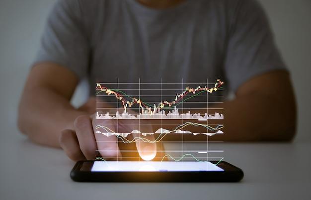 ハンドタッチスクリーンのスマートフォン技術でビジネスグラフをチェックする男性の使用