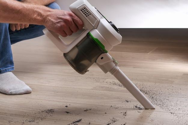 한 남자가 가방이없는 수직 무선 진공 청소기를 사용하여 바닥을 청소합니다.