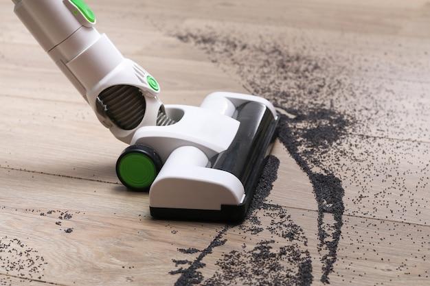한 남자가 가방없는 수직 무선 진공 청소기를 사용하여 바닥을 청소합니다.