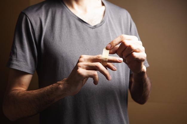 한 남자가 손가락의 손상된 피부에 석고를 사용합니다.