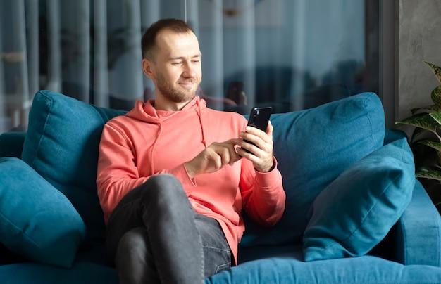 Мужчина использует смартфон на своем домашнем диване, отдыхая дома, звонки приложений