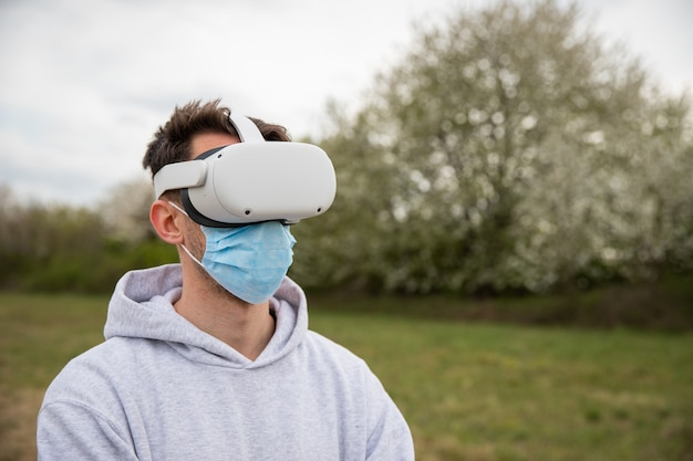 外でバーチャル リアリティ ヘッドセットを使用している男性が、サージカル マスクを着用しています。