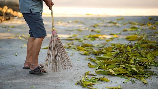 Мужчина использует веник. подметайте листья во внутреннем дворике из цемента, чтобы убрать грязь.