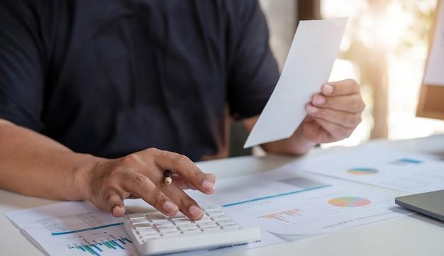 職場で経費請求書を計算するために計算機を使用している男性。ビジネスコンセプト。
