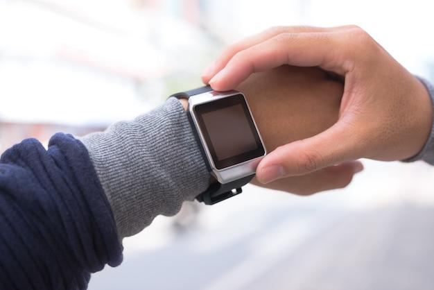 スマートウォッチアプリを屋外で使用している男性。