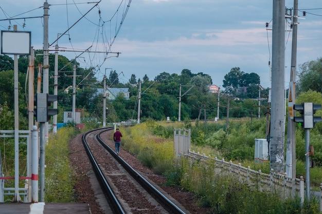 저녁에 철도 트랙을 걷는 남자.