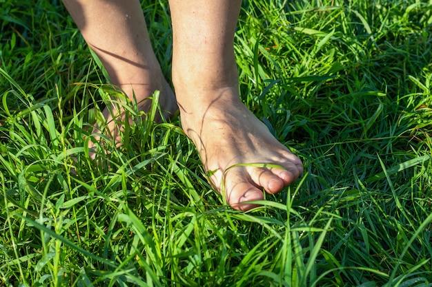 朝、緑の芝生の上を裸足で歩く男