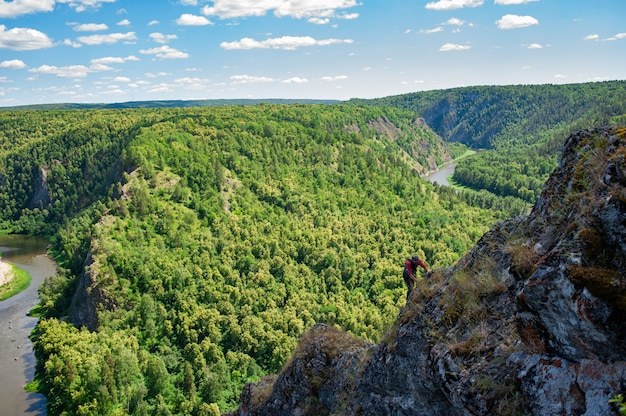 남자는 강 계곡에 대하여 산에 걷는다