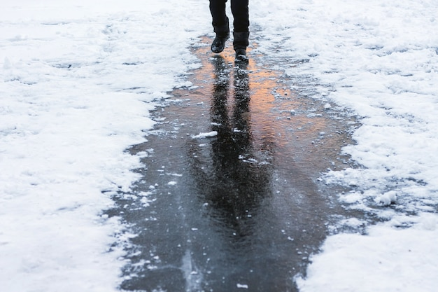 Человек идет по льду, фигура человека отражается и дорассовое небо