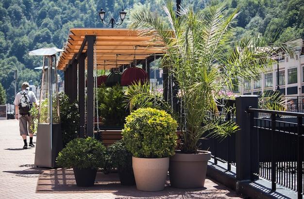 山のリゾートタウンにある緑豊かなレストランを通り過ぎる男。