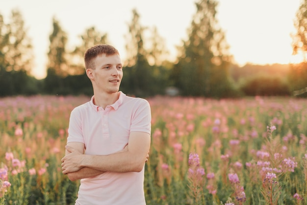 男は花の牧草地を歩きます。愛と春の開花
