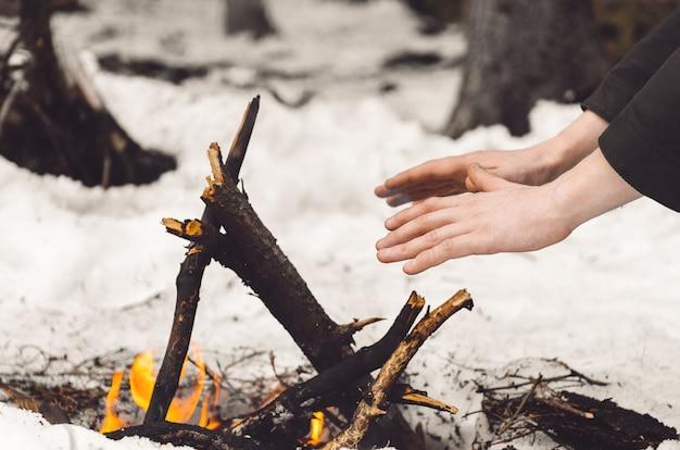 Мужчина греет руки у горящего костра зимой.