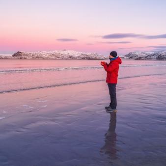 한 남자가 차와 함께 워밍업을 합니다. 추운 황량한 북극 해안에서 따뜻한 차.