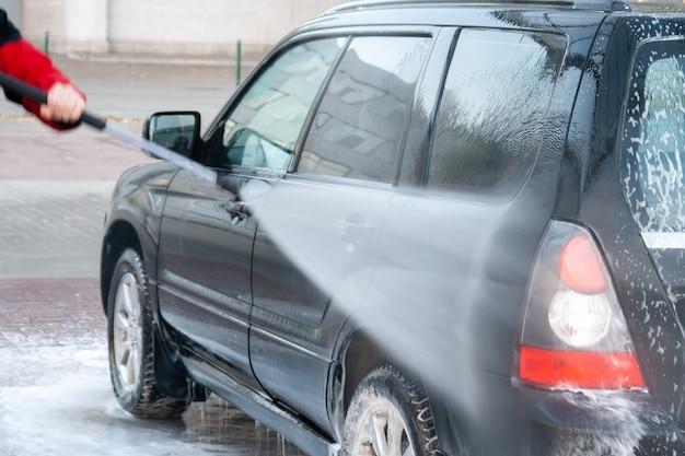 男性がセルフサービスの洗車場で黒い車を強い水で洗います。背面図