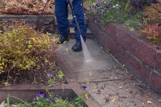 Мужчина моет садовую дорожку мойкой высокого давления. осенние работы в саду.