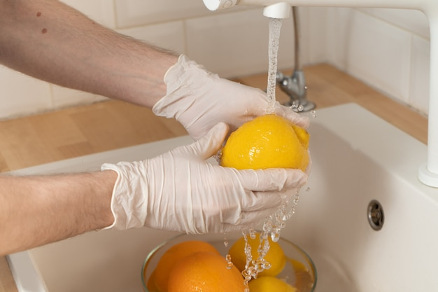 男は手袋の中の洗剤でレモンを洗います。若者は流行時に果物や野菜を殺菌します。使い捨て手袋の手のクローズアップは、流水でレモンを洗います。