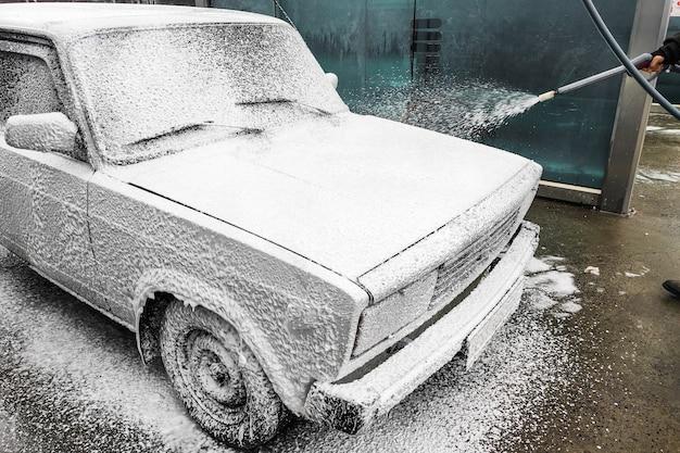 Мужчина моет белую машину. специальная пенка для умывания удаляет загрязнения.