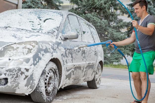 Мужчина моет машину в раковине самообслуживания летом на открытом воздухе