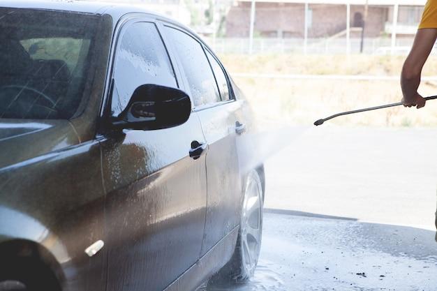 남자는 물로 그의 차를 씻는다