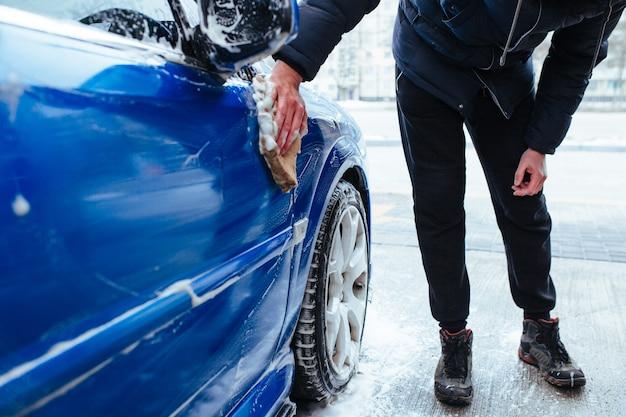 男が手ぬぐいで車を洗う。セルフサービス洗車