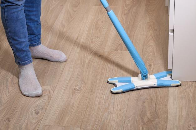 Мужчина моет полы шваброй в комнате. под кроватью. очистка.