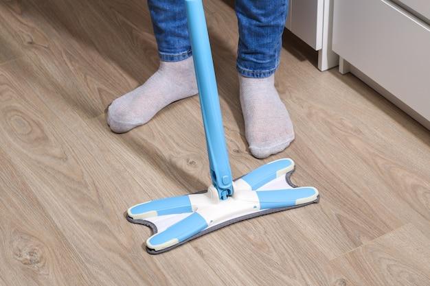 한 남자가 방에서 걸레로 바닥을 닦습니다. 침대 밑에. 청소.