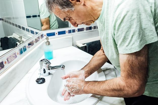 コロナウイルスに感染しないように、トイレで手を石鹸で洗う男性。 covidのコンセプト。