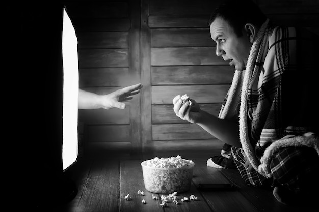 白黒テレビでホラー映画を見ている男