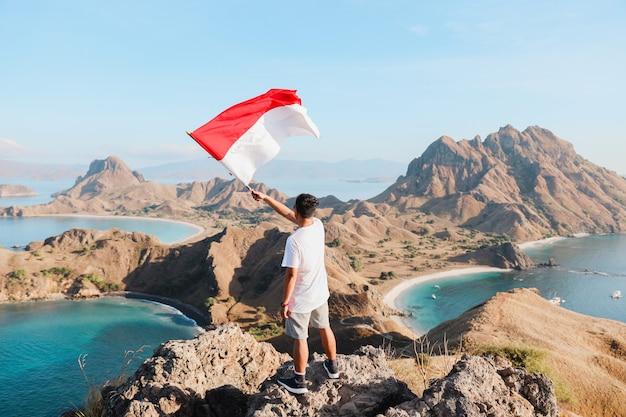 파다르 섬 라부안 바조의 꼭대기 언덕에서 인도네시아 국기를 흔드는 남자