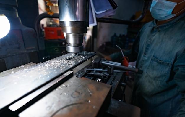 男性は、製粉機で作業するサージカルマスクを着用しています。金属ワークを切断するためのツール。超硬合金フライス盤を備えた縦型フライス盤。鉄鋼製造業。製粉プロセス。