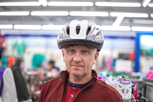 자전거 헬멧을 착용하는 남자. 상점에서 쇼핑
