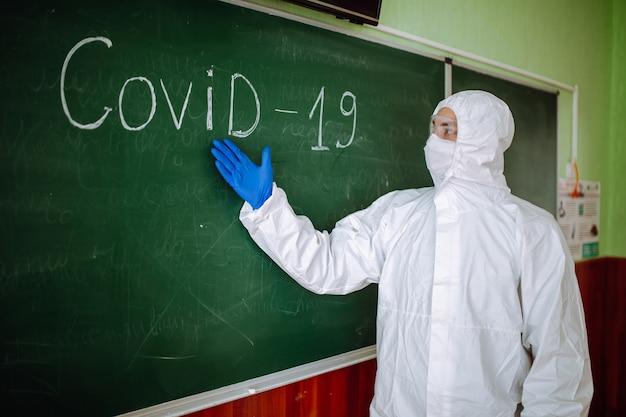 保護用の抗菌スーツを着た男性が、covid-19という言葉が書かれた緑色の黒板の近くに立っています。消毒作業員が学校でのコロナウイルスの脅威について説明します。生徒と学生のヘルスケア。