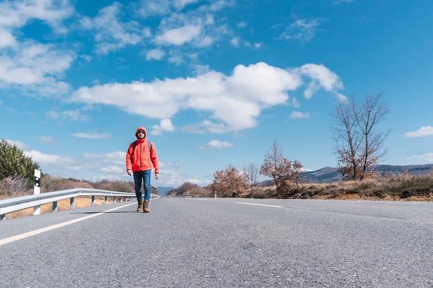 アスファルト道路のコピースペースを歩いている赤いジャケットとジーンズを着た男