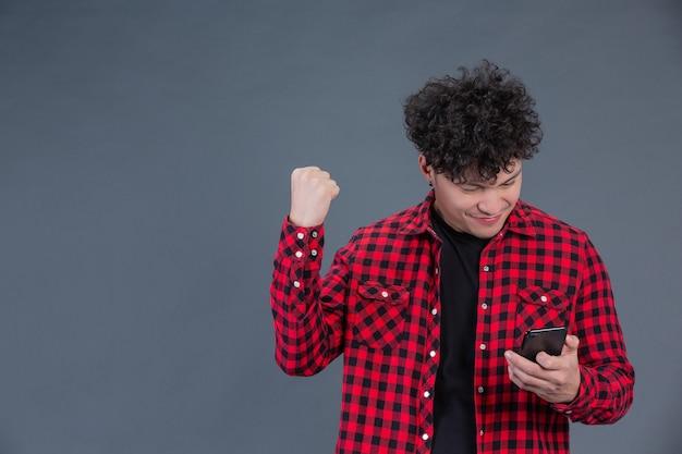 Мужчина в красной клетчатой рубашке со смартфоном