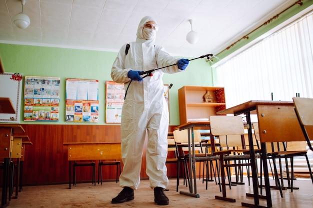 Мужчина в дезинфицирующем оборудовании и защитном костюме дезинфицирует класс, чтобы предотвратить распространение коронавируса среди студентов и учеников. концепция здравоохранения и профилактики covid-19.