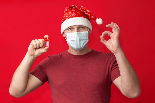 Мужчина в шляпе санты и медицинской маске держит вакцину от covid-19 и показывает знак ок на красном фоне. рождество и новый год во время концепции пандемии.
