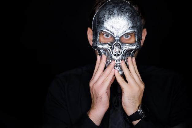Мужчина в маске скелета поправляет руками