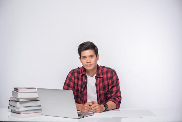 Мужчина в полосатой рубашке работает с ноутбуком.