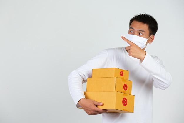 白いtシャツを着た男性が茶色のポストボックスを持って物を届けますジェスチャーや表情を作ります。