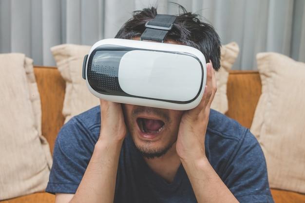 Человек, носящий и играющий в виртуальную реальность, наслаждаясь контентом на коричневом диване