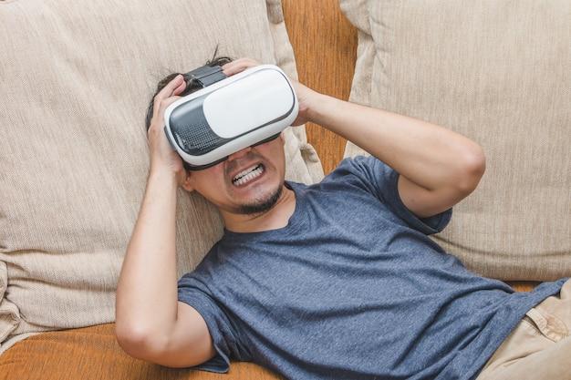 Человек, носящий и играющий в виртуальную реальность, наслаждаясь испуганным контентом на коричневом диване