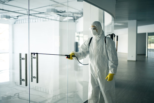 Мужчина в дезинфекционном костюме распыляет дезинфицирующее средство на ручки стеклянных дверей в пустом торговом центре, чтобы предотвратить распространение covid-19. осведомленность о здоровье, чистота, концепция защиты.