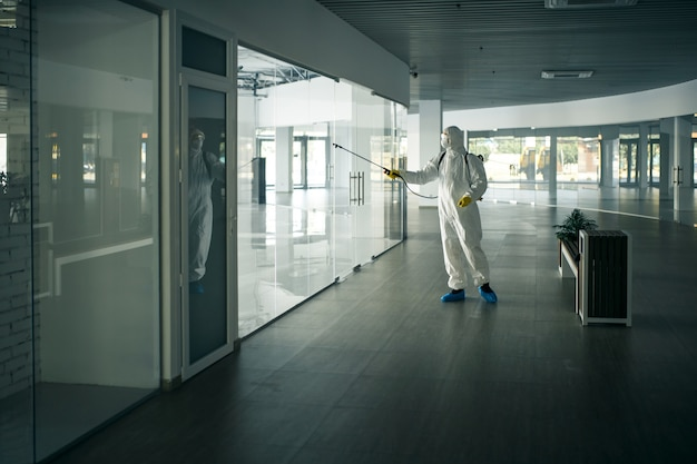 Covid-19の蔓延を防ぐために、空のショッピングモールでガラスのドアのハンドルに消毒剤をスプレーする消毒スーツを着た男性。健康意識、クリーン、防衛の概念。