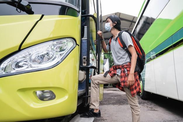 Мужчина в маске садится в автобус. мужчина в маске с рюкзаком с рюкзаком садится в автобус у терминала.